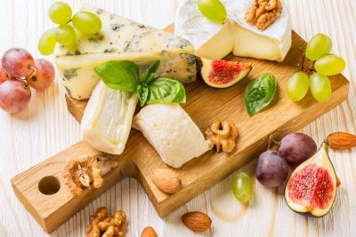 Cheese platter with figs, grapes and nuts on white wooden